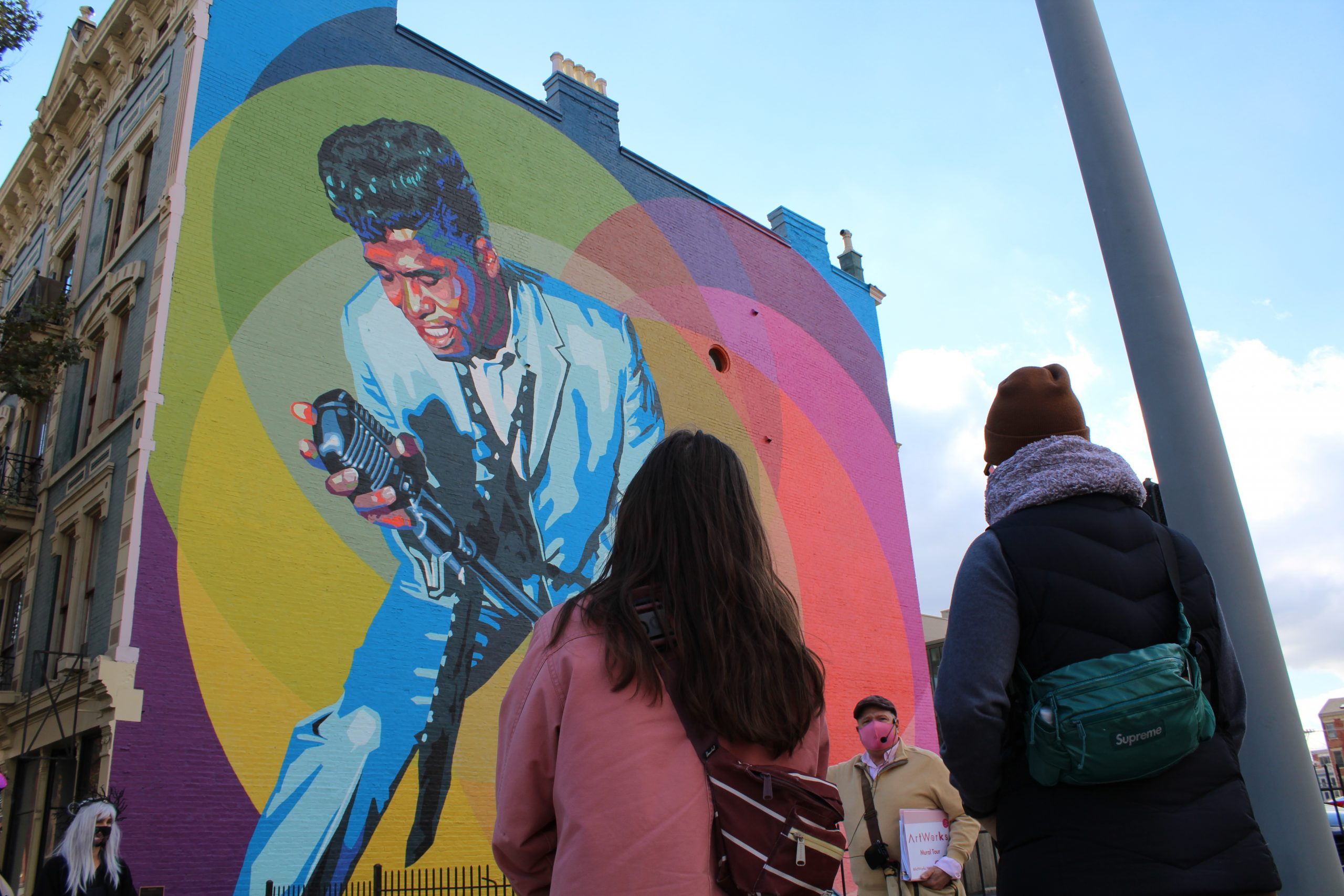 Small group of three in front of the Mr. Dynamite mural, honoring James Brown. Mural shows Brown singing into a vintage mic surrounded by colorful spotlight circles.