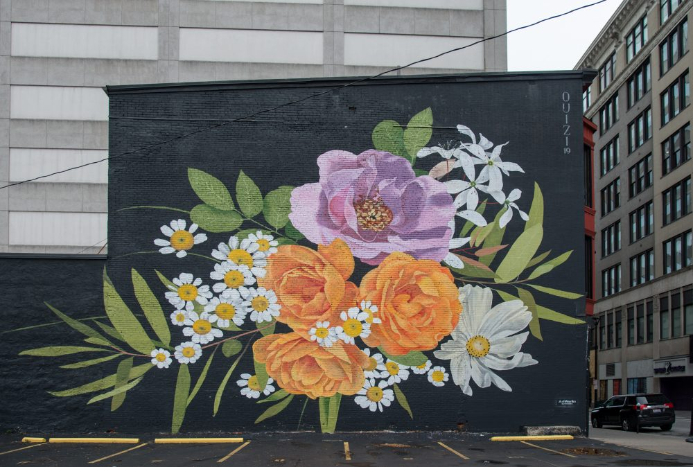 Building mural of yellow, while and pink flowers on a black background.